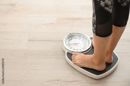 Cuadros en Lienzo  Woman measuring her weight using scales on wooden floor