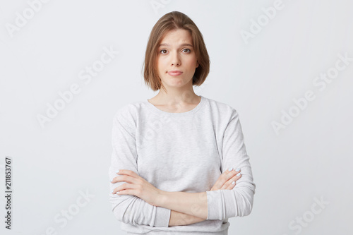 Unhappy dissatisfied young woman in longsleeve standing with hands folded and fe Tapéta, Fotótapéta