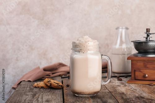 Mason jar with delicious milk shake on wooden table Fototapeta