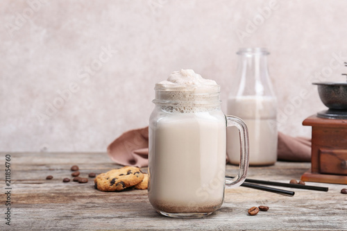 Foto Mason jar with delicious milk shake on wooden table
