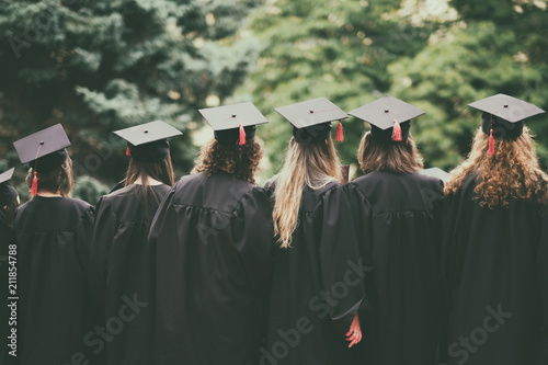 group of graduated students back view standing ourside between trees Canvas Print