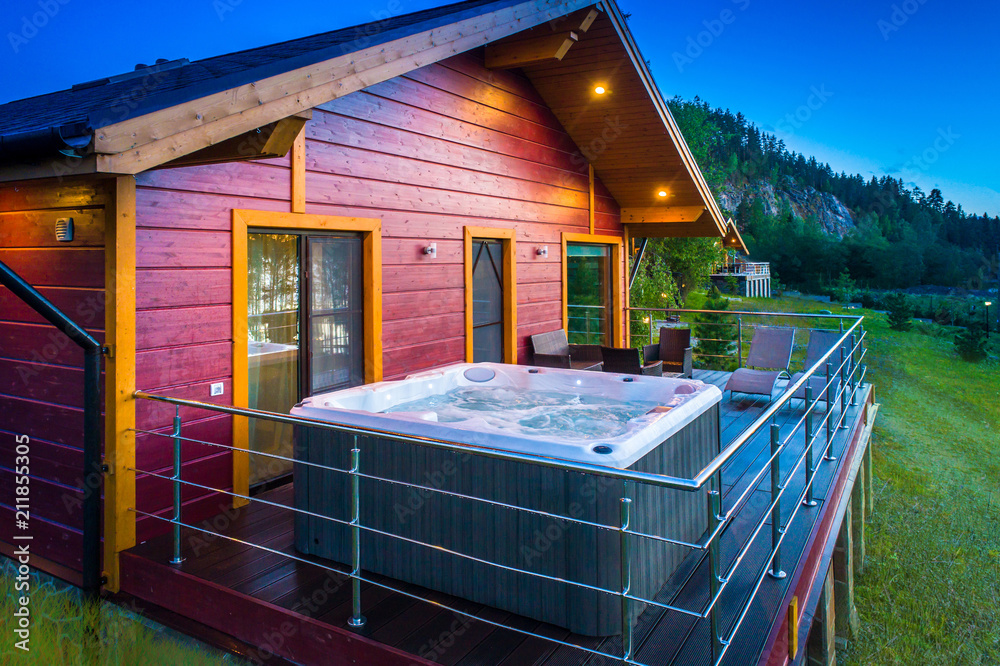 Fototapeta Cottage with Jacuzzi. Hot tub on the balcony of the house. Vacation home. Cottage with balcony.