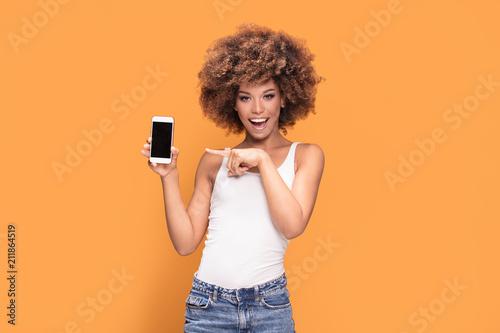 Fotografía  Smiling afro girl showing blank screen mobile phone.