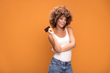 Young Afro Girl Holding Credit Card On Yellow Background.