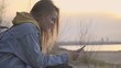 Nature and technologies. Young woman chatting hold in hand cellphone slow motion. Female hiker smile by the reading messages and answer to friend. At background beautiful scene of sunset above the sea