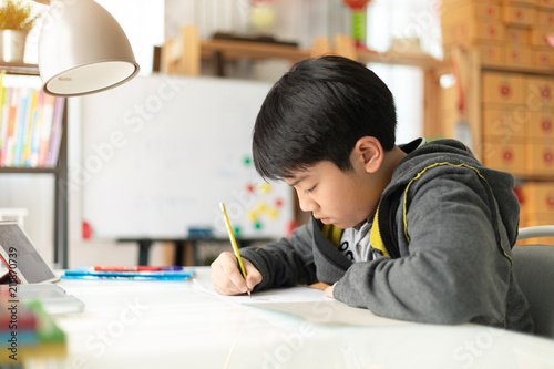 Young asian teenage student doing homework .