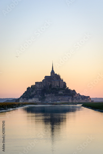 Fotografia The silhouette of the famous Mont Saint-Michel tidal island in Normandy, France, at sunrise and high tide, reflecting in the still waters of the Couesnon river with the warm colors of the sky