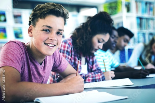 Fotografie, Obraz  Portrait of happy schoolboy studying in library