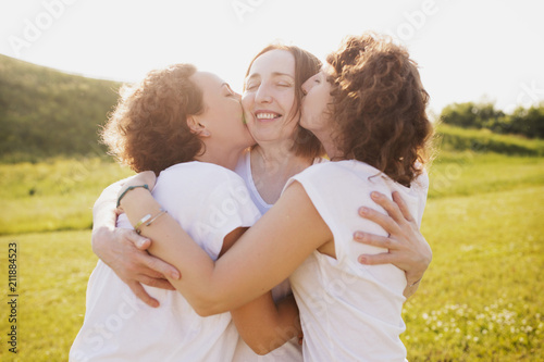 Fotomural Happy beautiful mother woman hugging her beautiful curly daughters in white T-sh