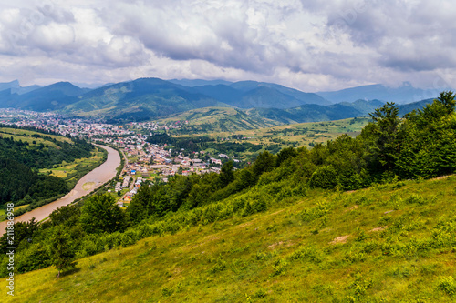 Foto op Canvas Bleke violet The top view of a rural village located between a small fast river and huge green mountain ranges