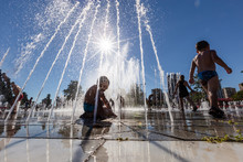 Unidentified Kids Playing In The Fountain In City Park