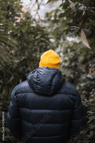 Mann mit gelber Mütze und blauer Daunenkjacke im Palmenhaus in Wien Schönbrunn