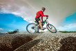 Low, wide angle portrait against explose blue sky of mountain biker going downhill. Cyclist in red sport equipment and helmet slice bike through the ground at risk of accident