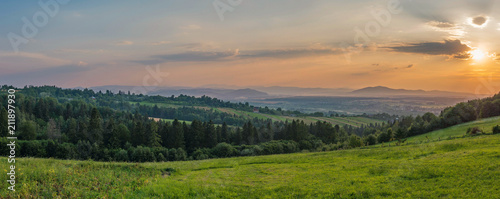 Foto op Canvas Zalm Sunset in the evening sky against the backdrop of green hills and massive vast mountains