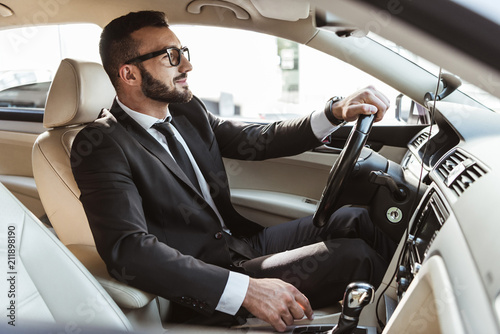 Fotografía side view of handsome driver in suit driving car