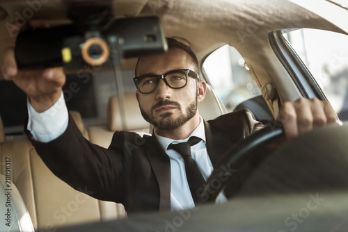 handsome driver in suit driving car and fixing mirror Tableau sur Toile