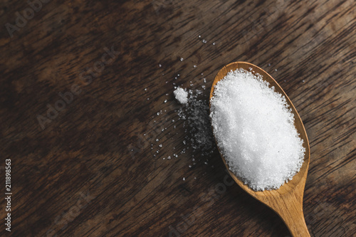 Spoon of fine granulated sugar on wood table. Wallpaper Mural