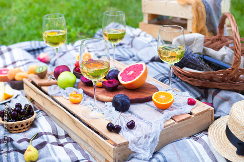 Aluminium Prints Picnic background with white wine and summer fruits on green grass, summertime party