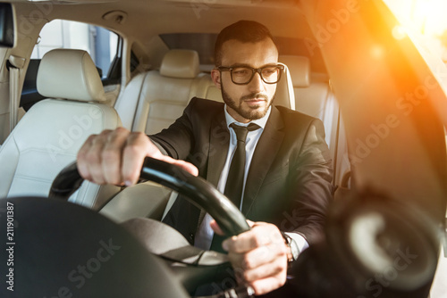 Obraz na plátne handsome driver in suit and glasses driving auto during sunset