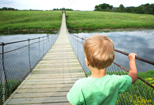 Fotografía  Cute toddler boy on a suspension bridge across the river
