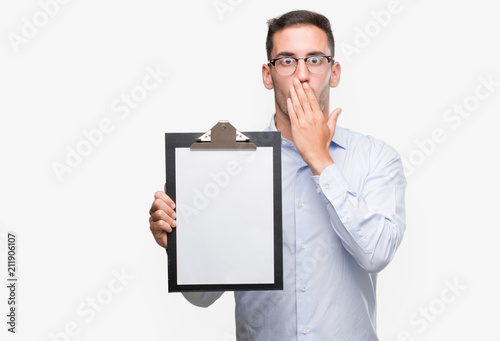 handsome young business man showing a clipboard cover mouth with