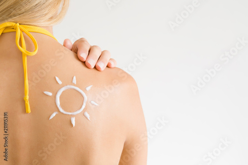 Sun shape created from sunscreen lotion on young woman's back. Skin protection. Safety sunbathing concept. Copy space. Empty place for text on light gray background.