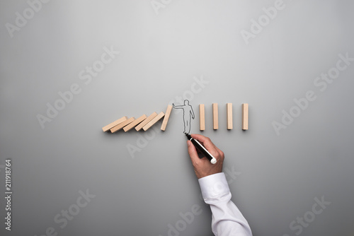 Fotografiet Man drawing the outline of a businessman stopping the domino effect