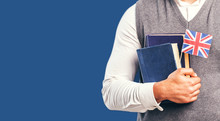 Man Wears Grey Sweater Vest Holds English Books And Flag Before Dark Blue Studio Background, Language Learning Concept