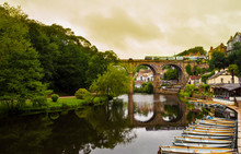 View Of The Nidd River And Rowing Boats From The Ruins Of Knaresborough Castle With The Train Passing Through The Old Bridge In A Cloudy Day.