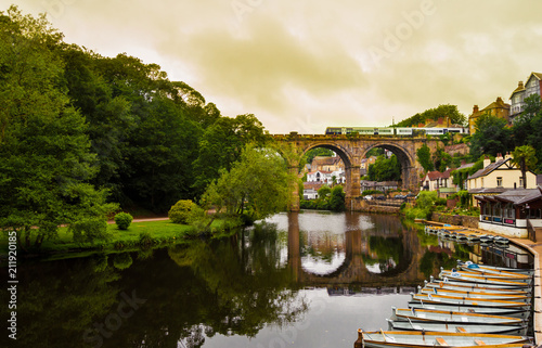 Canvastavla View of the Nidd River and rowing boats from the ruins of Knaresborough Castle with the train passing through the old bridge in a cloudy day