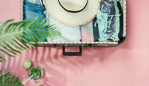 Foto Leaf of fern, tropical detox water and open suitcase with clothes on pastel pink