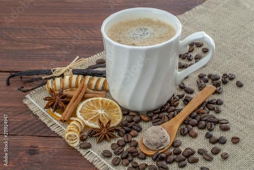 taza de cafe sobre una mesa de madera rústica decorada con granos, canela, y vainilla