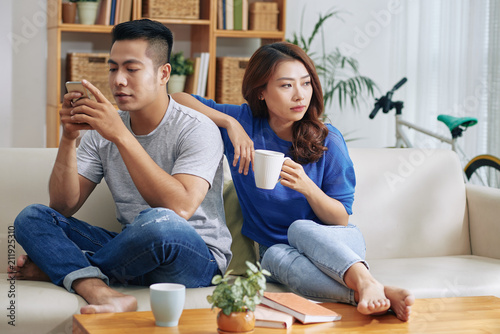 Asian couple sitting on couch and man surfing smartphone while woman looking bor Wallpaper Mural