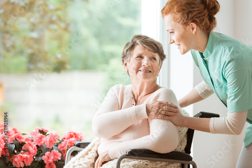 Fotografia  Young nurse helping an elderly woman in a wheelchair