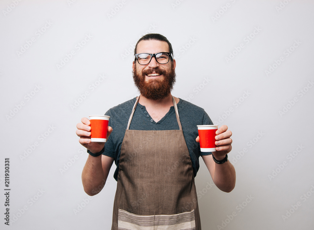 Fototapeta Happy bearded barista wearing apron and glasses on white background, holding two red paper cups. Hipster man smiling at the camera.