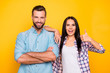 canvas print picture - Portrait of comic couple in casual clothes, handsome man holding arms crossed, beautiful woman gesturing thumb up and winking with one eye isolated on bright yellow background