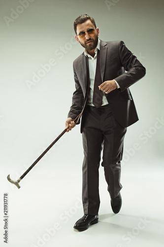 Obraz na plátně  The barded man in a suit holding cane.