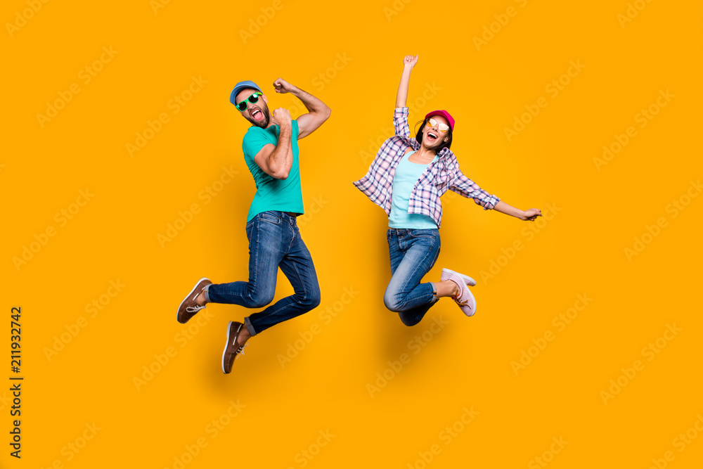Fototapeta Portrait of funky active couple jumping with raised fists celebrating victory wearing casual clothes isolated on vivid yellow background
