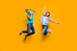 canvas print picture - Portrait of funky active couple jumping with raised fists celebrating victory wearing casual clothes isolated on vivid yellow background