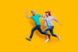Leinwanddruck Bild - Portrait of athletic sportive students running fast wearing jeans casual clothes isolated on bright yellow background. Inspiration motivation concept