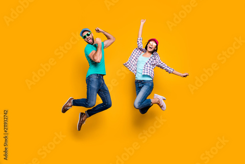 Photo  Portrait of funky active couple jumping with raised fists celebrating victory we