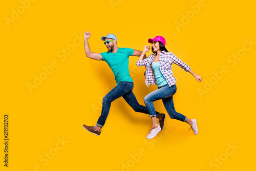 Portrait of athletic sportive students running fast wearing jeans casual clothes isolated on bright yellow background. Inspiration motivation concept