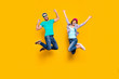 Portrait of lucky successful couple jumping with raised fists celebrating victory wearing denim outfit isolated on bright yellow background. Energy luck success concept