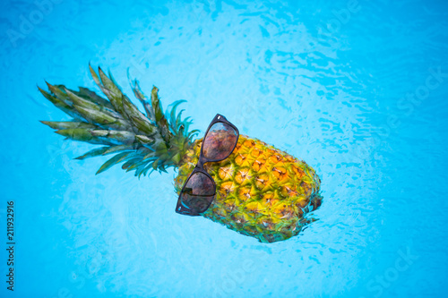 Fotografía Pineapple with sunglasses in the pool, holiday feeling