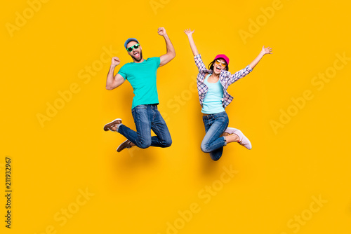 Obraz Portrait of lucky successful couple jumping with raised fists celebrating victory wearing denim outfit isolated on bright yellow background. Energy luck success concept - fototapety do salonu