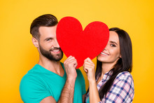 Portrait Of Lovely Cheerful Couple Looking Out Big Carton Paper Heart Figure Having Beaming Smiles Isolated On Bright Yellow Background. Fall In Love True Feelings Concept