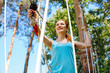 Enjoying extreme experience. Cheerful young woman climbing at a rope park and smiling happily while having a day off at an adventure park