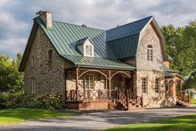 Canadiana Cottage Style Fieldstone House With Seam Sheet Metal Roof