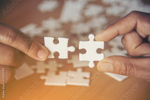 Fototapety, obrazy: Hand holding jigsaw puzzles, Business partnership concept.