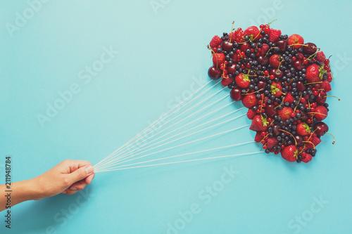 Ręki mienie szybko się zwiększać robić jagody na błękitnym papierowym tle. Pojęcie zdrowego odżywiania. Płaskie leżało. Toned
